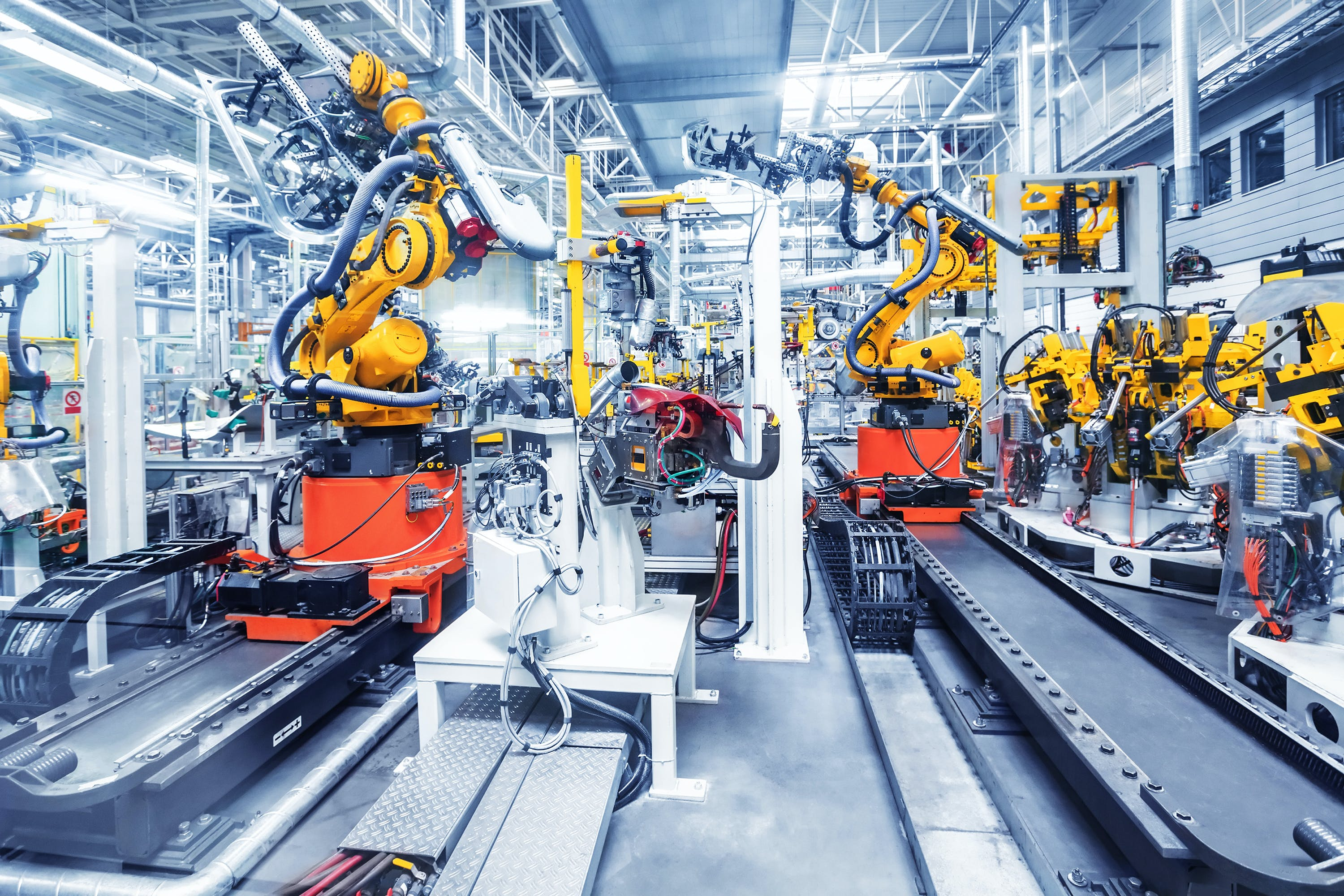 Inside of a factory with robotic arms assembling large machinery