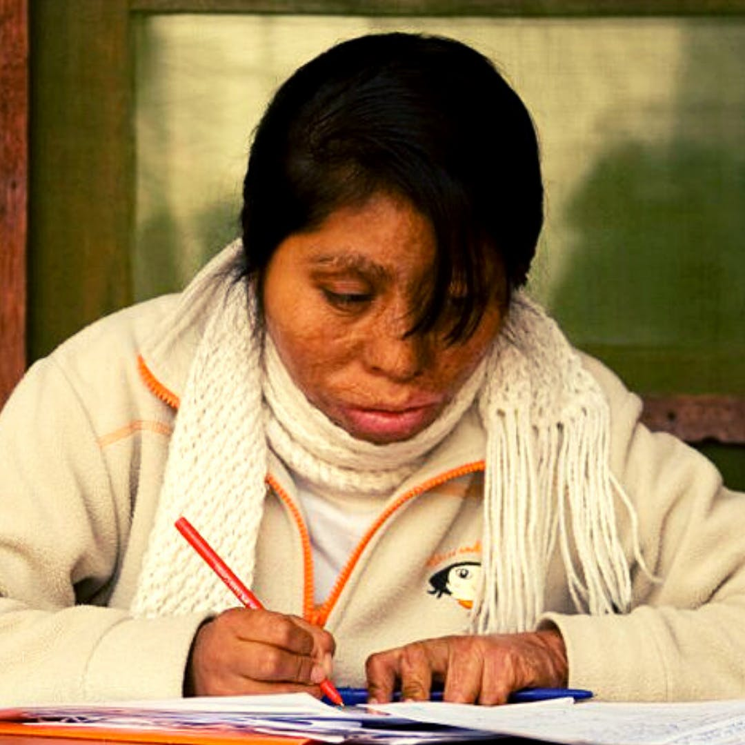 Violeta,  a HOPE Scholar studying at a table receives our most needed solution,  Financial Aid .