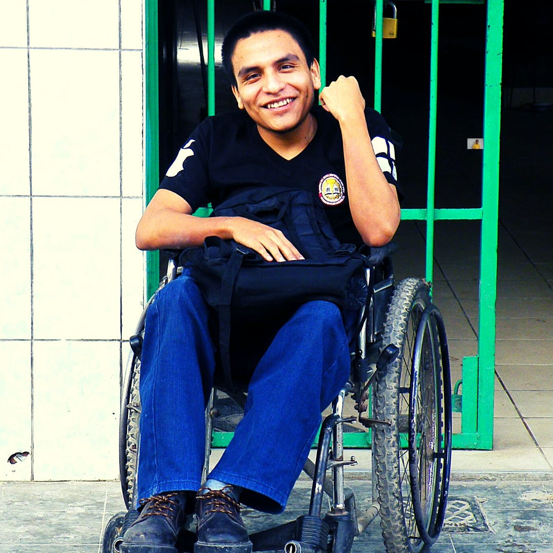 Juan Daniel, who is a HOPE Scholar smiling about education possibilities while in wheelchair outside his school.